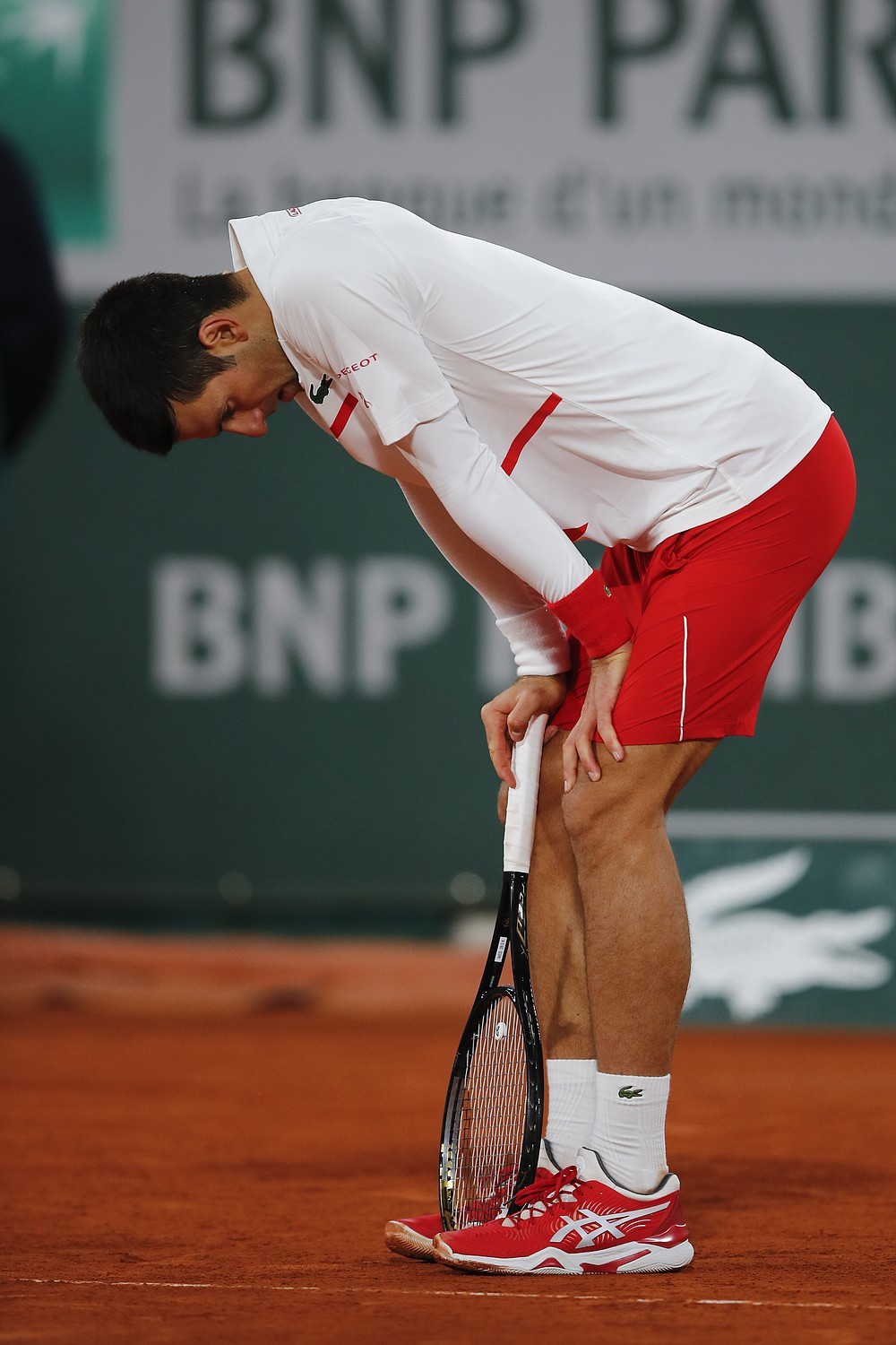 Serbia's Novak Djokovic leans on his racket in the quarterfinal match of the French Open tennis tournament against Spain's Pablo Carreno Busta at the Roland Garros stadium in Paris, France, Wednesday, Oct. 7, 2020. (AP Photo/Christophe Ena)