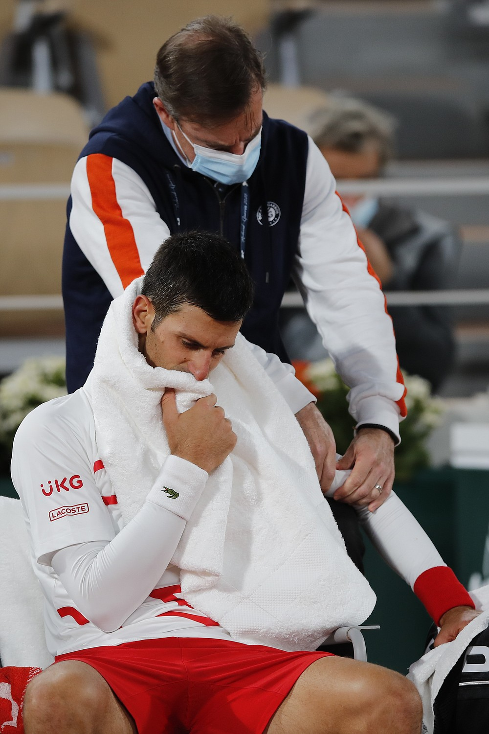 Serbia's Novak Djokovic receives medical assistance for a left arm injury in the quarterfinal match of the French Open tennis tournament against Spain's Pablo Carreno Busta at the Roland Garros stadium in Paris, France, Wednesday, Oct. 7, 2020. (AP Photo/Christophe Ena)