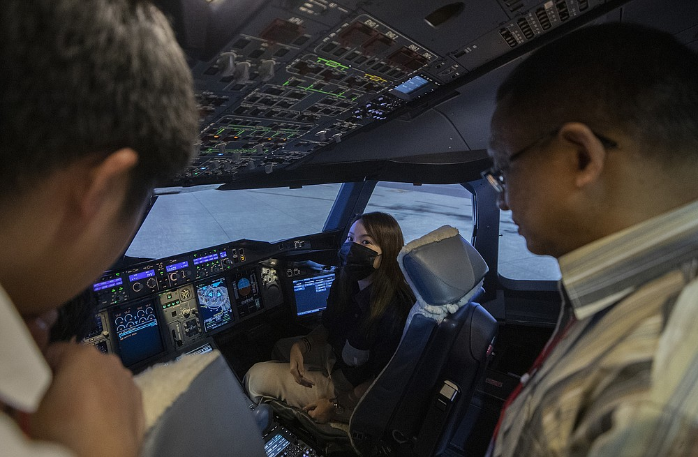 A customer sits in a Boeing A380 flight simulator for a flight experience at the Thai Airways head office in Bangkok, Thailand on Oct. 3, 2020. The airline is selling time on its flight simulators to wannabe pilots while its catering division is serving meals in a flight-themed restaurant complete with airline seats and attentive cabin crew. The airline is trying to boost staff morale, polish its image and bring in a few pennies, even as it juggles preparing to resume international flights while devising a business reorganization plan. (AP Photo/Sakchai Lalit)