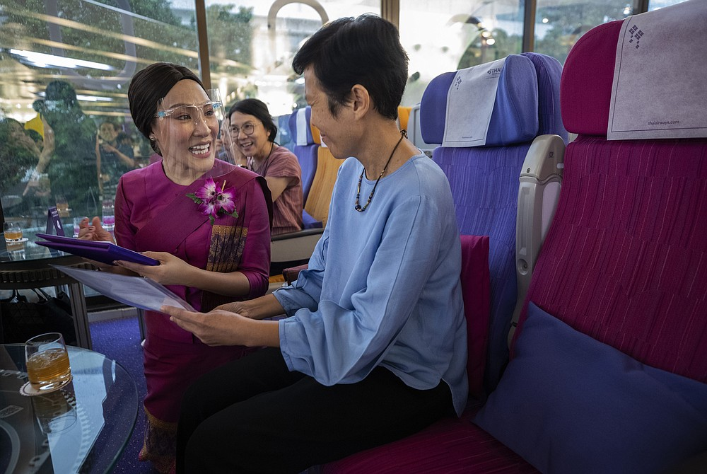 A customer orders meal to a flight attendant in a flight-themed restaurant at the Thai Airways head office in Bangkok, Thailand on Oct. 3, 2020. The airline is selling time on its flight simulators to wannabe pilots while its catering division is serving meals in a flight-themed restaurant complete with airline seats and attentive cabin crew. The airline is trying to boost staff morale, polish its image and bring in a few pennies, even as it juggles preparing to resume international flights while devising a business reorganization plan.  (AP Photo/Sakchai Lalit)