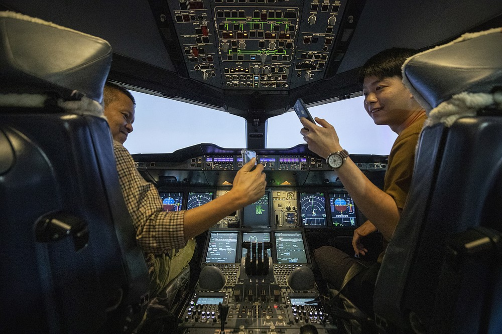 Customers take selfie photos in a Boeing A380 flight simulator during a flight experience at the Thai Airways head office in Bangkok, Thailand on Oct. 3, 2020. The airline is selling time on its flight simulators to wannabe pilots while its catering division is serving meals in a flight-themed restaurant complete with airline seats and attentive cabin crew. The airline is trying to boost staff morale, polish its image and bring in a few pennies, even as it juggles preparing to resume international flights while devising a business reorganization plan.  (AP Photo/Sakchai Lalit)