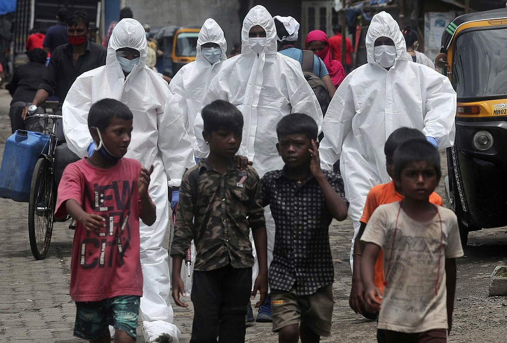 FILE - In this Friday, July 10, 2020 file photo, health workers wearing protective clothing arrive to screen people for COVID-19 symptoms at a slum in Mumbai, India. Up to 150 million people could slip into extreme poverty, living on less than $1.90 a day, by late next year depending on how badly economies shrink during the COVID-19 pandemic, the World Bank said Wednesday, Oct. 7, 2020 in an outlook grimmer than before. (AP Photo/Rafiq Maqbool, File)