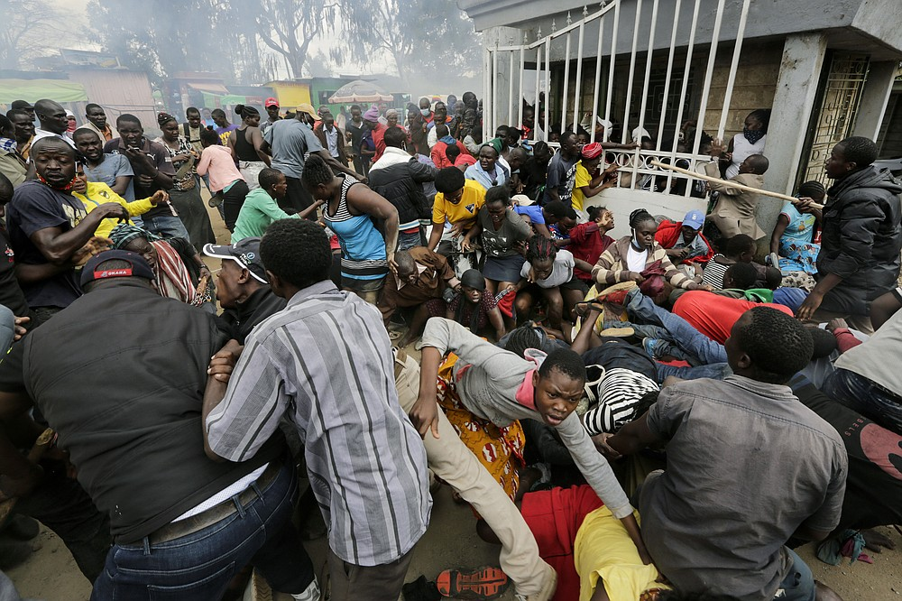 FILE - In this Friday, April 10, 2020 file photo, residents desperate for a planned distribution of food for those suffering under Kenya's coronavirus-related movement restrictions push through a gate and create a stampede, causing police to fire tear gas, at a district office in the Kibera slum of Nairobi. Up to 150 million people could slip into extreme poverty, living on less than $1.90 a day, by late next year depending on how badly economies shrink during the COVID-19 pandemic, the World Bank said Wednesday, Oct. 7, 2020 in an outlook grimmer than before. (AP Photo/Khalil Senosi, File)