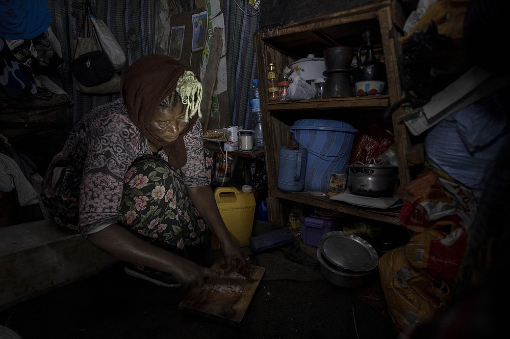 FILE - In this Friday, June 26, 2020 file photo, mother of two Amsale Hailemariam, a domestic worker who lost work because of the coronavirus, prepares food for her family in her small tent in the capital Addis Ababa, Ethiopia. Up to 150 million people could slip into extreme poverty, living on less than $1.90 a day, by late next year depending on how badly economies shrink during the COVID-19 pandemic, the World Bank said Wednesday, Oct. 7, 2020 in an outlook grimmer than before. (AP Photo/Mulugeta Ayene, File)
