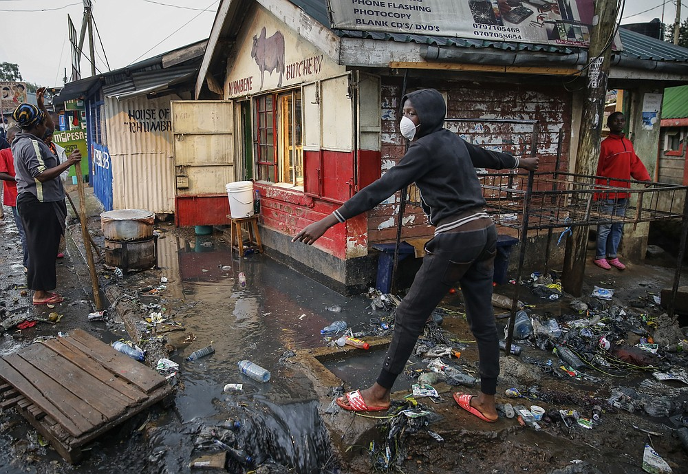 FILE - In this Thursday, March 26, 2020 file photo, a boy wears a mask as a preventative measure against the spread of the new coronavirus, as he navigates a flood of water mixed with garbage following heavy rains, in the Kibera slum, or informal settlement, of Nairobi, Kenya. Up to 150 million people could slip into extreme poverty, living on less than $1.90 a day, by late next year depending on how badly economies shrink during the COVID-19 pandemic, the World Bank said Wednesday, Oct. 7, 2020 in an outlook grimmer than before. (AP Photo/Brian Inganga, File)