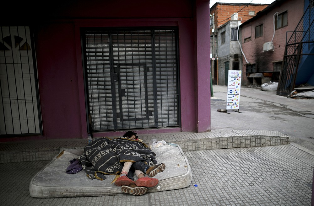 """FILE - In this Wednesday, May 6, 2020 file photo, homeless women sleep outside on a mattress in the """"Villa 31"""" neighborhood during a government-ordered lockdown to curb the spread of the new coronavirus in Buenos Aires, Argentina. Up to 150 million people could slip into extreme poverty, living on less than $1.90 a day, by late next year depending on how badly economies shrink during the COVID-19 pandemic, the World Bank said Wednesday, Oct. 7, 2020 in an outlook grimmer than before. (AP Photo/Natacha Pisarenko, File)"""