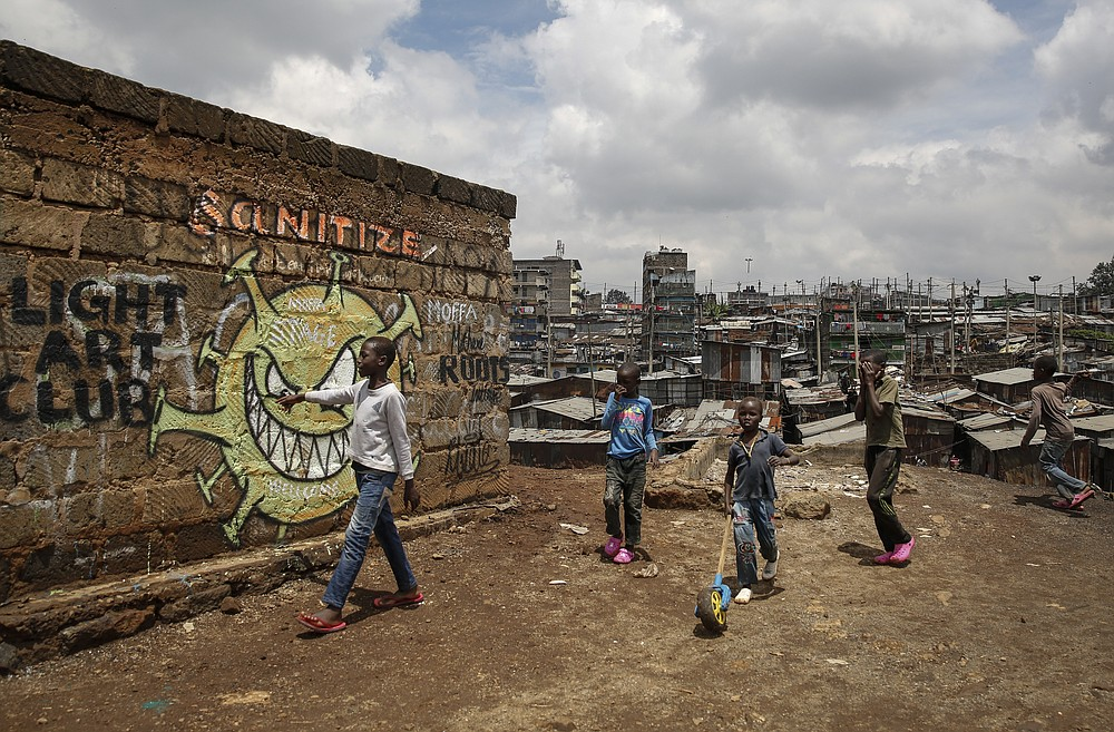 FILE - In this April 22, 2020, file photo, children walk past an informational mural depicting the coronavirus and warning people to sanitize to prevent its spread, painted by graffiti artists from the Mathare Roots youth group, in the Mathare slum, or informal settlement, of Nairobi, Kenya. Up to 150 million people could slip into extreme poverty, living on less than $1.90 a day, by late next year depending on how badly economies shrink during the COVID-19 pandemic, the World Bank said Wednesday, Oct. 7, 2020 in an outlook grimmer than before. (AP Photo/Brian Inganga, File)