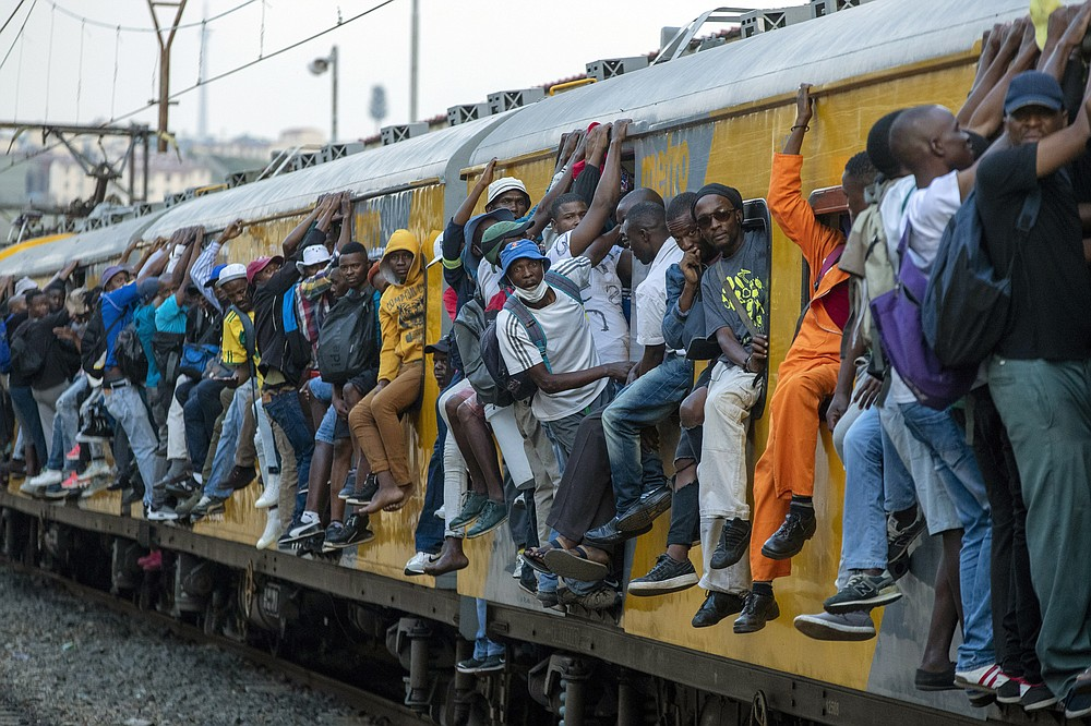 FILE - In this Monday, March 16, 2020 file photo, train commuters hold on to the side of an overcrowded passenger train in Soweto, South Africa. Up to 150 million people could slip into extreme poverty, living on less than $1.90 a day, by late next year depending on how badly economies shrink during the COVID-19 pandemic, the World Bank said Wednesday, Oct. 7, 2020 in an outlook grimmer than before. (AP Photo/Themba Hadebe, File)
