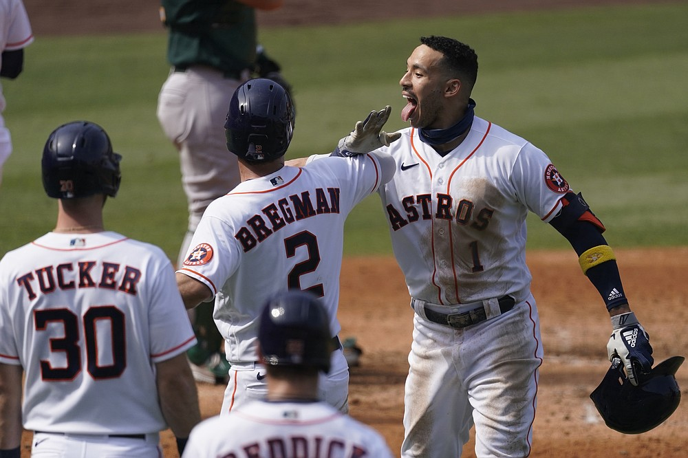 Houston Astros' Carlos Correa, right, celebrates after hitting a three-run home run that scored Kyle Tucker (30) and Alex Bregman (2) during the fourth inning of Game 4 of a baseball American League Division Series against the Oakland Athletics in Los Angeles, Thursday, Oct. 8, 2020. (AP Photo/Ashley Landis)