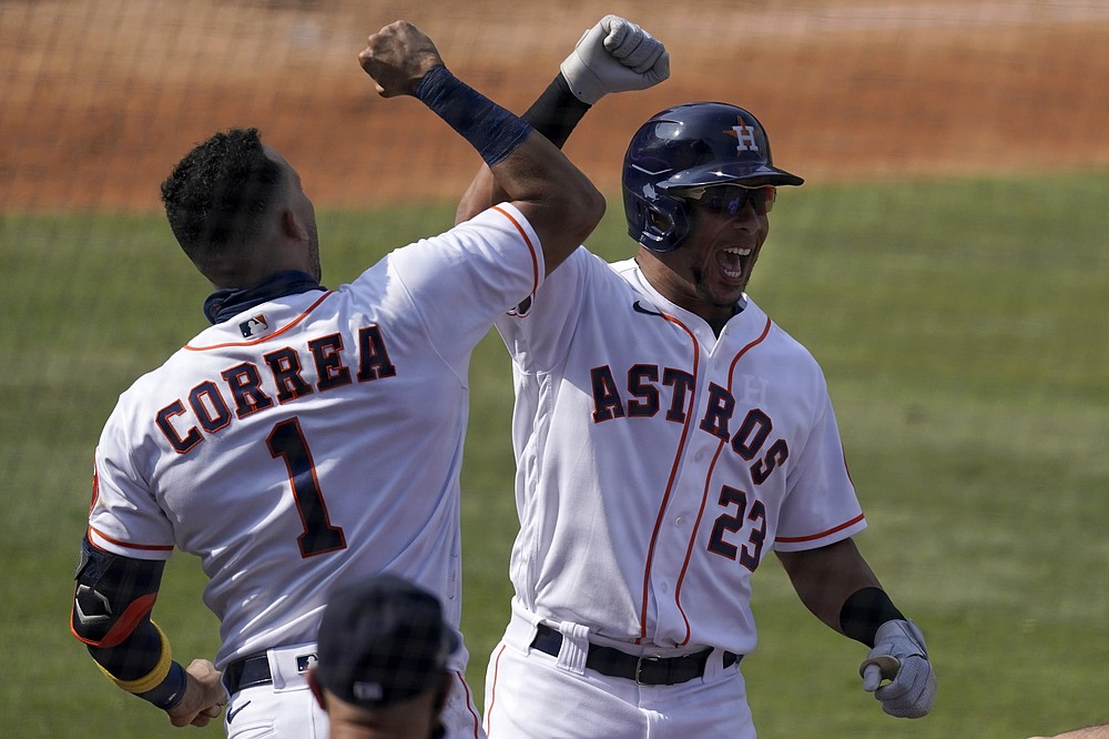 Houston Astros' Michael Brantley (23) celebrates with Carlos Correa after hitting a solo home run against the Oakland Athletics during the fifth inning of Game 4 of a baseball American League Division Series in Los Angeles, Thursday, Oct. 8, 2020. (AP Photo/Ashley Landis)
