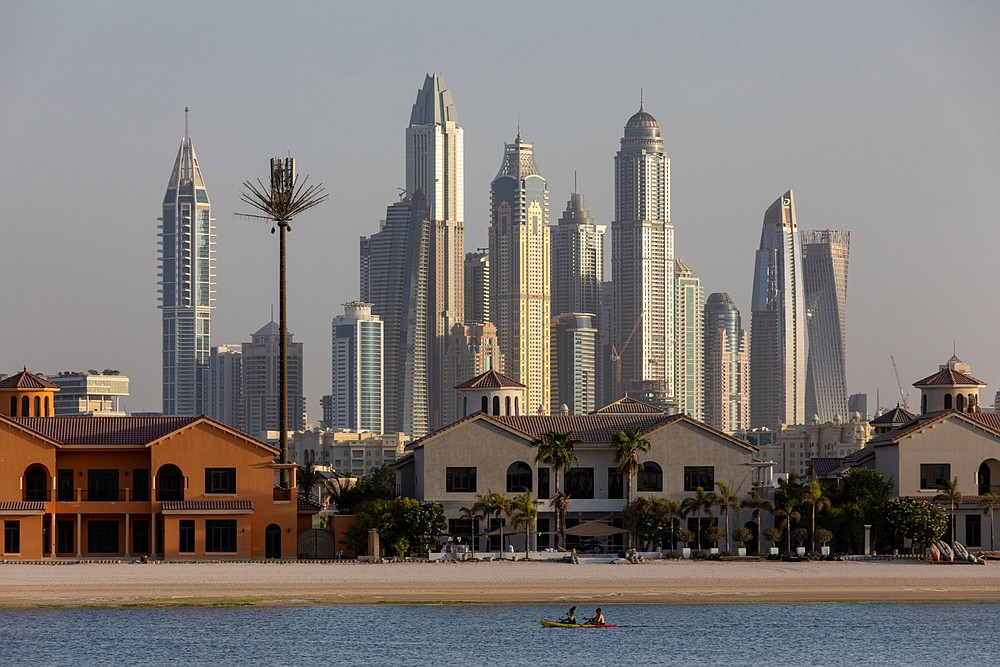 A kayak passes by residential villas on the waterside of the Palm Jumeirah as residential skyscrapers stand beyond in the Dubai Marina district in Dubai, United Arab Emirates, on Sept. 5, 2020. MUST CREDIT: Bloomberg photo by Christopher Pike.