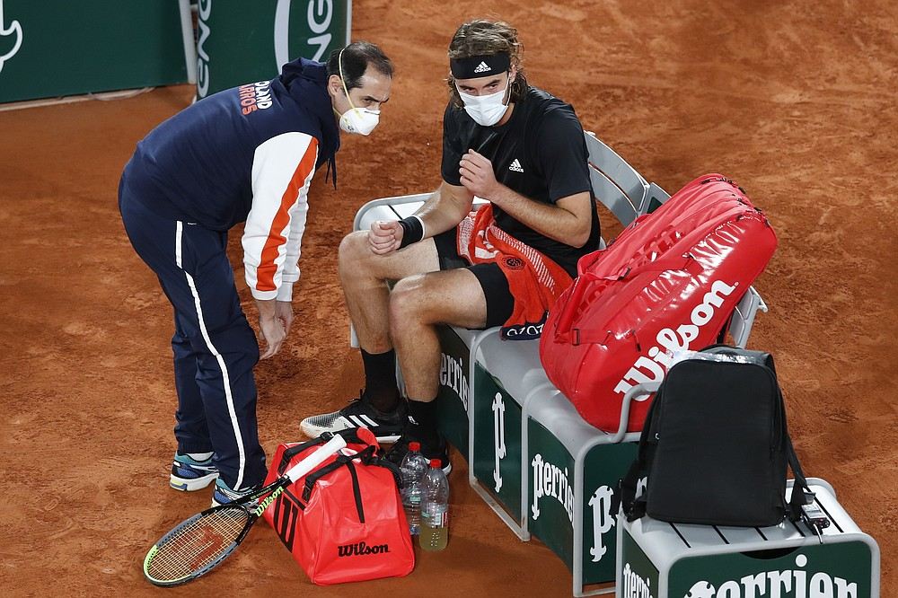 Greece's Stefanos Tsitsipas receives medical assistance in the semifinal match of the French Open tennis tournament against Serbia's Novak Djokovic at the Roland Garros stadium in Paris, France, Friday, Oct. 9, 2020. (AP Photo/Alessandra Tarantino)