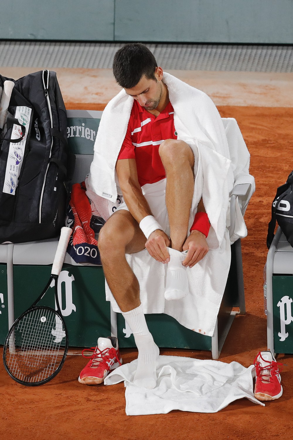 Serbia's Novak Djokovic puts on a sock in the semifinal match of the French Open tennis tournament against Greece's Stefanos Tsitsipas at the Roland Garros stadium in Paris, France, Friday, Oct. 9, 2020. (AP Photo/Christophe Ena)