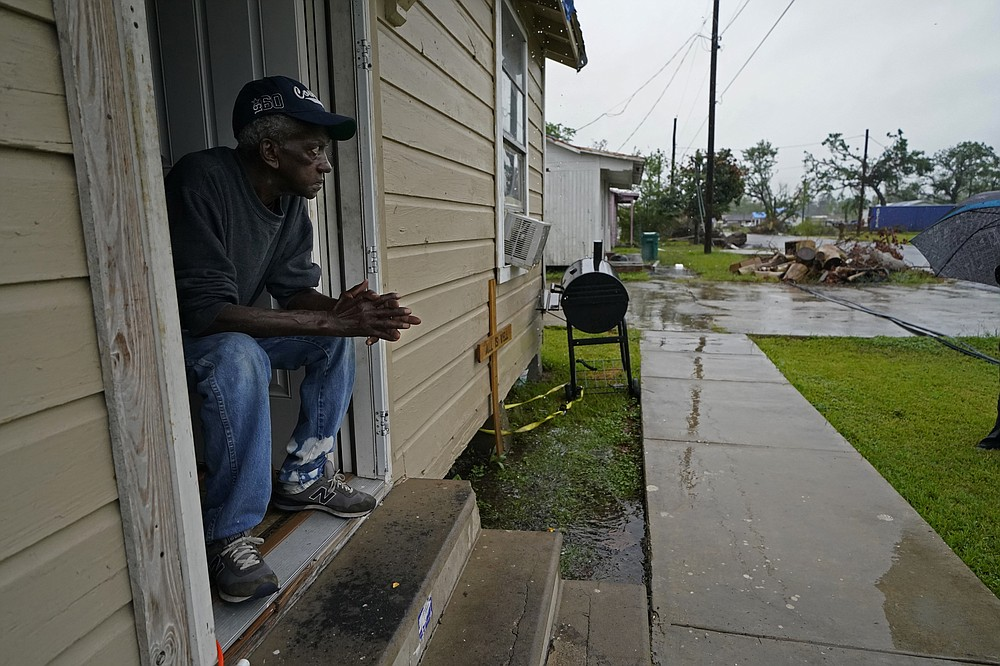 Earnst Jack, whose home was severely damaged from Hurricane Laura, sits in his front doorway as he waits for the arrival of Hurricane Delta expected to make landfall later in the day in Lake Charles, La., Friday, Oct. 9, 2020. Debris from Hurricane Laura is piled near the street. (AP Photo/Gerald Herbert)