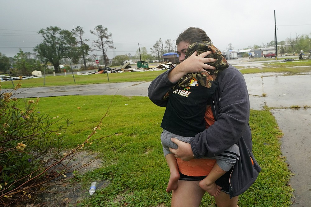 Danielle Fontenot runs to a relative's home in the rain with her son Hunter ahead of Hurricane Delta, Friday, Oct. 9, 2020, in , La. Forecasters said Delta — the 25th named storm of an unprecedented Atlantic hurricane season — would likely crash ashore Friday evening somewhere on southwest Louisiana's coast. (AP Photo/Gerald Herbert)