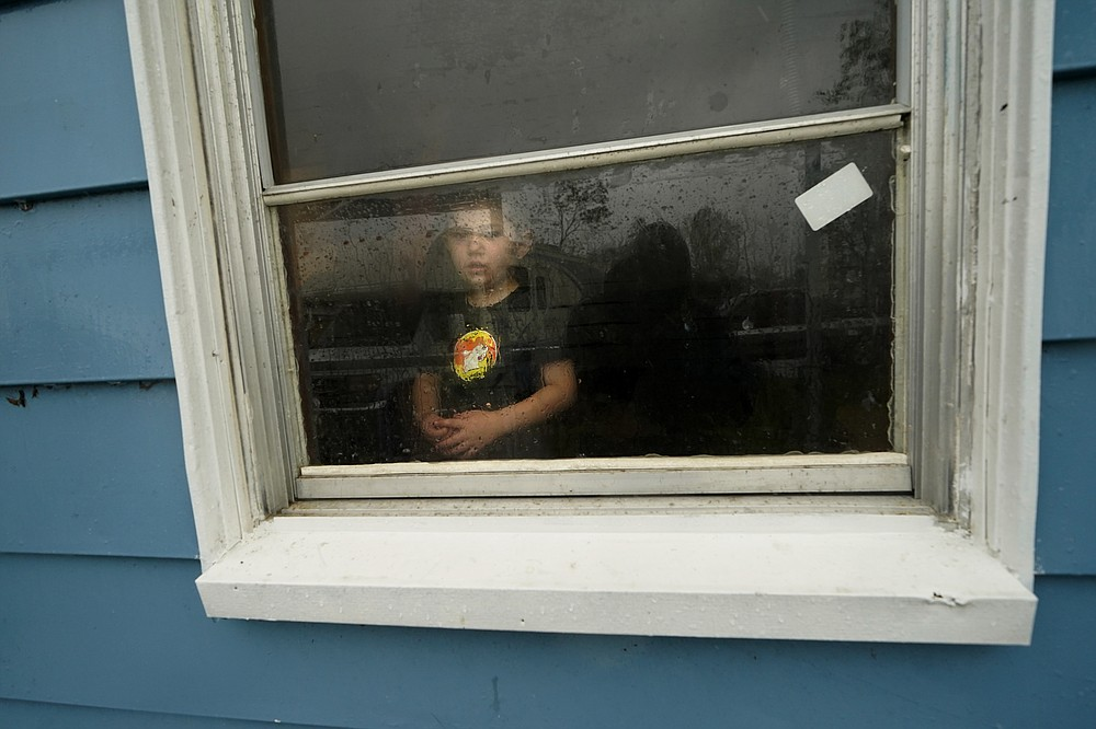 Hunter Daniel, 3, looks out the window of his uncle's house, to which his family temporarily relocated to ride out Hurricane Delta which is expected to make landfall later in the day, in Lake Charles, La., Friday, Oct. 9, 2020. (AP Photo/Gerald Herbert)
