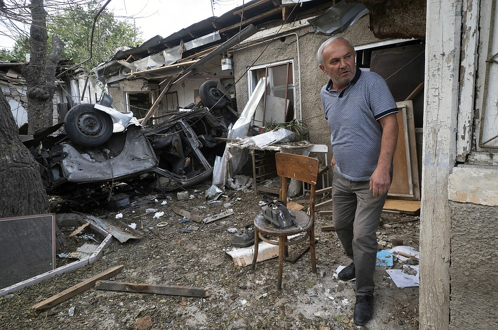 A man walks in the yard of a house destroyed by shelling by Azerbaijan's artillery during a military conflict in Stepanakert, the separatist region of Nagorno-Karabakh, Friday, Oct. 9, 2020. The latest outburst of fighting between Azerbaijani and Armenian forces began Sept. 27 and marked the biggest escalation of the decades-old conflict over Nagorno-Karabakh. The region lies in Azerbaijan but has been under control of ethnic Armenian forces backed by Armenia since the end of a separatist war in 1994. (AP Photo)