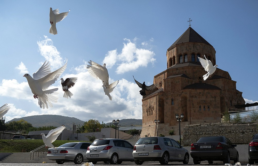 Pigeons fly near Holy Mother of God Cathedral in Stepanakert during a military conflict in the separatist region of Nagorno-Karabakh, Friday, Oct. 9, 2020. The latest outburst of fighting between Azerbaijani and Armenian forces began Sept. 27 and marked the biggest escalation of the decades-old conflict over Nagorno-Karabakh. The region lies in Azerbaijan but has been under control of ethnic Armenian forces backed by Armenia since the end of a separatist war in 1994. (AP Photo)