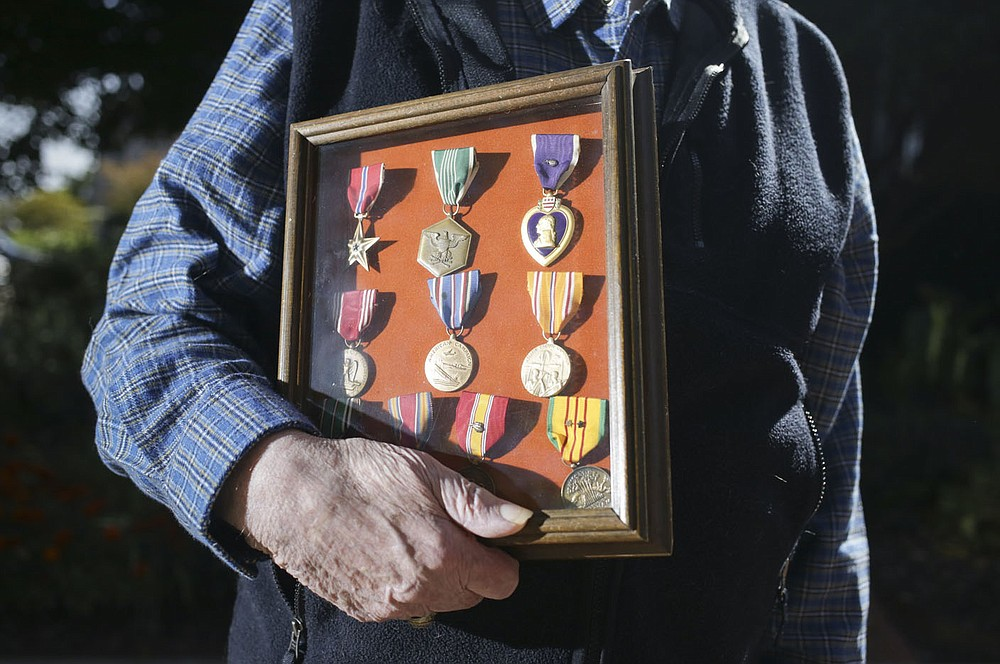 Albert King holds his medals, Friday, October 2, 2020 at the Fayetteville Square in Fayetteville. Check out nwaonline.com/2010010Daily/ for today's photo gallery.  (NWA Democrat-Gazette/Charlie Kaijo)
