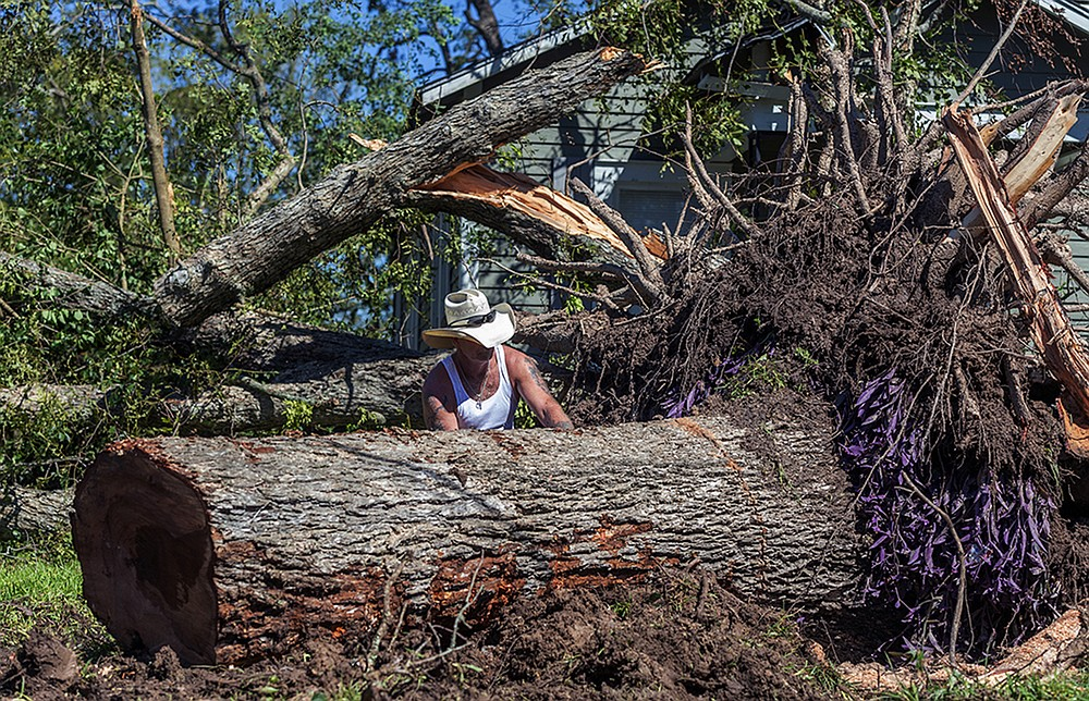 Michael McDonald clears trees after Hurricane Delta passed the area in Jennings, La., Saturday, Oct. 10, 2020.  The day after Hurricane Delta blew through besieged southern Louisiana, residents started the routine again: dodging overturned cars on the roads, trudging through knee-deep water to flooded homes with ruined floors and no power, and pledging to rebuild after the storm. (Scott Clause /The Daily Advertiser via AP)
