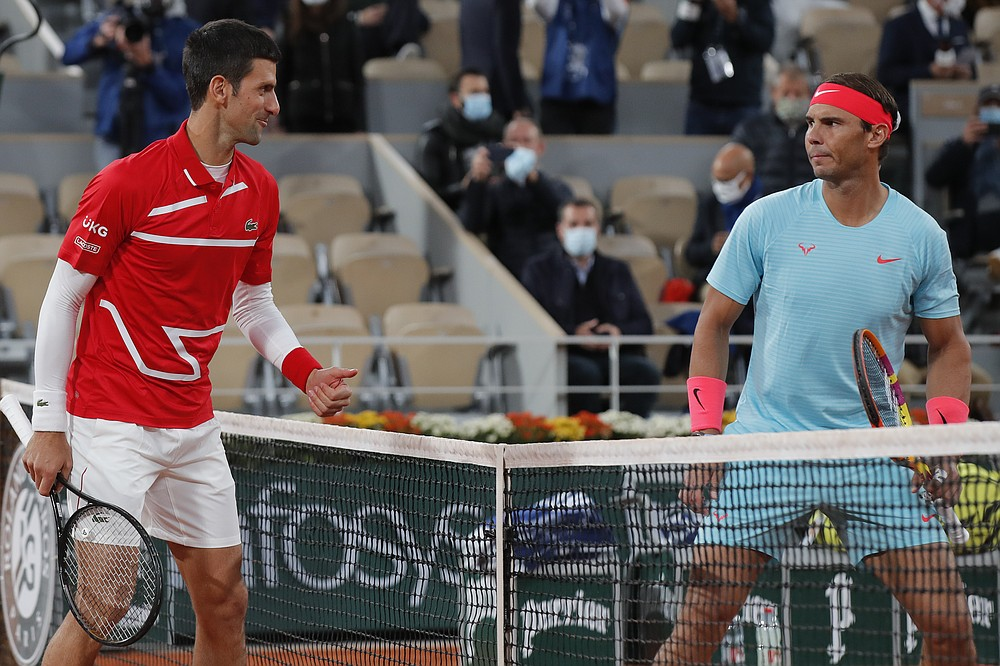 Serbia's Novak Djokovic, left, and Spain's Rafael Nadal look at each other as they pose for images prior to the final match of the French Open tennis tournament at the Roland Garros stadium in Paris, France, Sunday, Oct. 11, 2020. (AP Photo/Michel Euler)