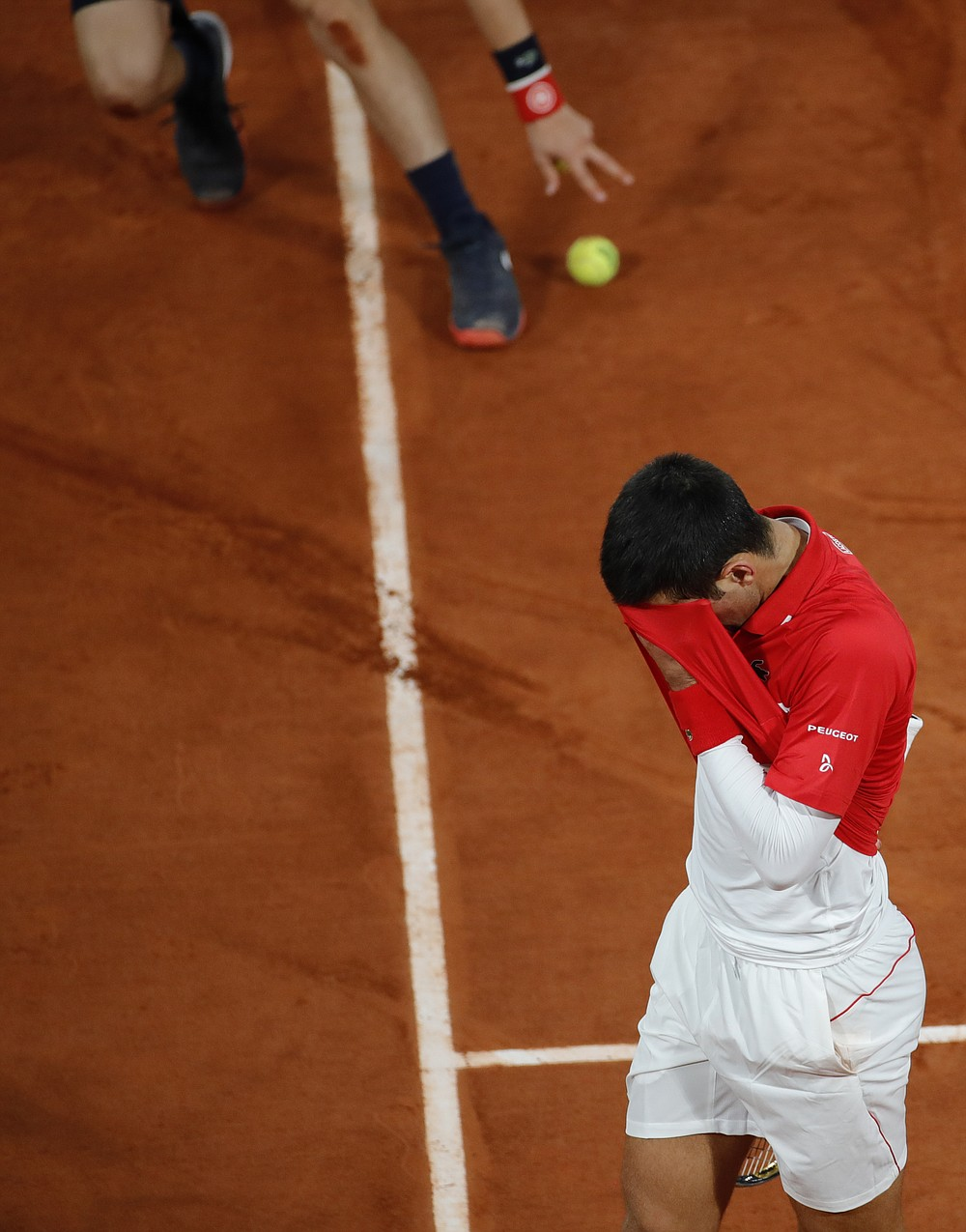 Serbia's Novak Djokovic reacts after missing a shot against Spain's Rafael Nadal in the final match of the French Open tennis tournament at the Roland Garros stadium in Paris, France, Sunday, Oct. 11, 2020. (AP Photo/Christophe Ena)