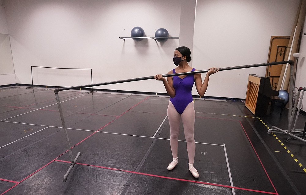 """Ballet student Micah Sparrow moves a bar into place to stretch in a classroom at the Texas Ballet Theatre, Wednesday, Oct. 7, 2020, in Fort Worth, Texas. For many, it's not Christmas without the dance of Clara, Uncle Drosselmeyer, the Sugar Plum Fairy, the Mouse King and, of course, the Nutcracker Prince. But this year the coronavirus pandemic has canceled performances of """"The Nutcracker"""" around the U.S. and Canada, eliminating a major and reliable source of revenue for dance companies already reeling financially following the essential shutdown of their industry.  (AP Photo/LM Otero)"""