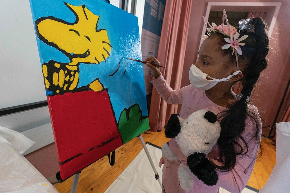 "Kaley Williams, 8, paints a panel of a ""Peanuts"" mural that will be placed in the outpatient pediatric floor of One Brooklyn Health at Brookdale Hospital, Thursday, Oct. 1, 2020, in the Brooklyn borough of New York. The virus pandemic won't stop Charlie Brown, Snoopy or the ""Peanuts"" gang from marking an important birthday and they're hoping to raise the spirits of sick kids while they celebrate. The beloved comic marks its 70th anniversary this week with new lesson plans, a new TV show and a philanthropic push that includes donating ""Peanuts"" murals for kids to paint in 70 children's hospitals around the globe, from Brooklyn to Brazil. (AP Photo/Mary Altaffer)"