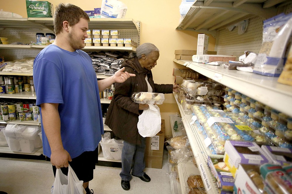 NWA Democrat-Gazette/DAVID GOTTSCHALK West Ralston (left) is assisted by Mary Macon, a volunteer at LifeSource, in collecting food items Monday, April 9, 2018, from the food pantry at the non profit in Fayetteville. The food pantry at LifeSource, offering donated food items, is open Monday, Wednesday and Thursday from 8:30 a.m. to 11:30 a.m., from 6:00 p.m. to 7:00p.m. for people who work during the day and Thurday at 5:30 p.m. for Spanish speaking families.