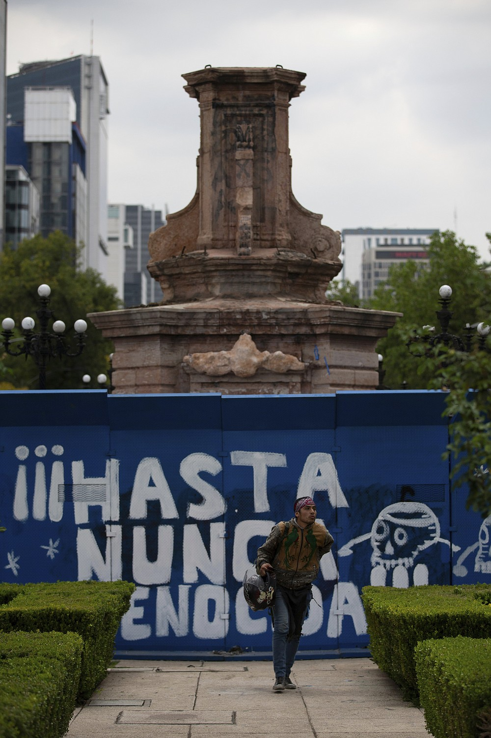 "A pedestrian walks past graffiti that reads in Spanish ""Never again genocider"" on a temporary metal barrier set up to protect the perimeter of the Christopher Columbus statue which was removed by authorities on Paseo de la Reforma in Mexico City, Monday, Oct. 12, 2020. Mexico has has a hard time dealing with the legacy of Cristopher Columbus, and officials are still being coy about why the statue was removed over the weekend. (AP Photo/Fernando Llano)"