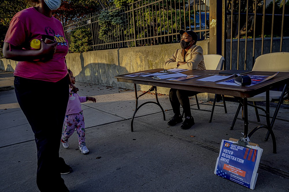 "A woman and child walk past Laurae Caruth, right, volunteer with Christian Cultural Center Social Justice Initiative's voter registration drive, as she sits at a table where she registers voters, Friday, Sept. 18, 2020, in the Brooklyn borough of New York. ""I'm out here volunteering because of how important it is to exercise the right to vote,"" Caruth said. In recent election cycles, predominantly Black congregations across the country have launched get-out-the-vote campaigns commonly referred to as ""souls to the polls."" But instead of packing buses and vans to shuttle people to early voting sites this year, church leaders say they are organizing caravans for absentee ballot drop-offs and in-person early voting. (AP Photo/Bebeto Matthews)"