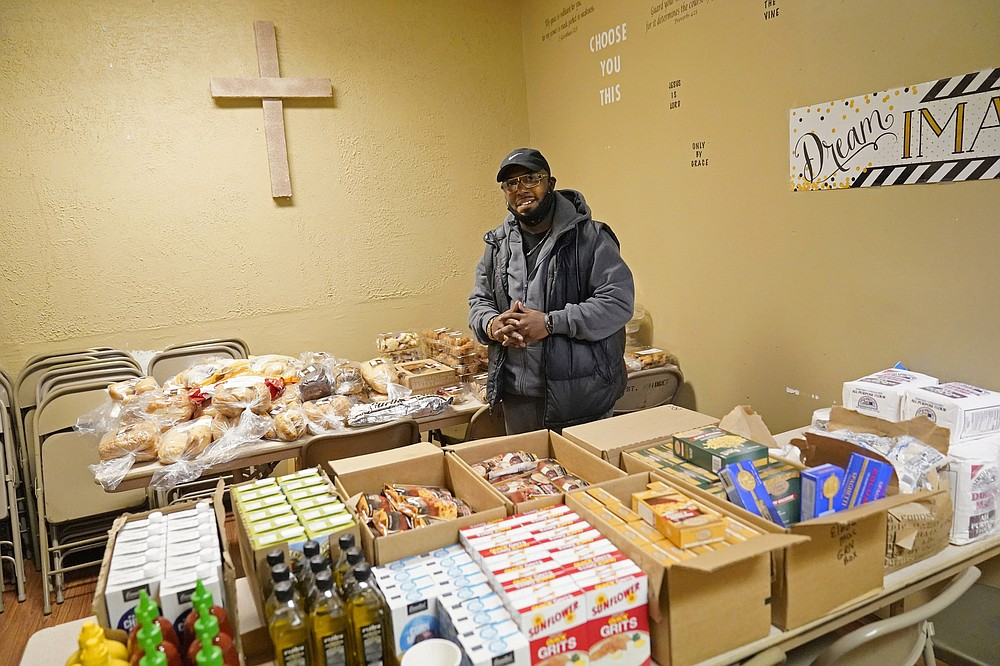 Bishop Divar L. Bryant Kemp poses at the New Mount Calvary Baptist Church food shelf, Thursday, Oct. 1, 2020, in North Minneapolis. In addition to the food shelf, Kemp makes a plea year-round to both his congregants and others outside of his church to get out and vote, emphasizing the efforts of past civil rights leaders that fought for Black citizens to receive that right. (AP Photo/Jim Mone)