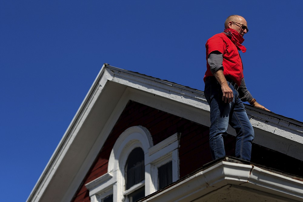 Gary Zaremba stands on the roof of a property he oversees, while they replace the roof, Wednesday, Oct. 7, 2020, in Dayton, Ohio. Seven months after the pandemic began, landlords face an even more uncertain future. Zaremba, who owns and and manages 350 apartment  units spread out over 100 buildings in Dayton, Ohio, said he has been working with struggling tenants and directs them to social service agencies for additional help.  (AP Photo/Aaron Doster)