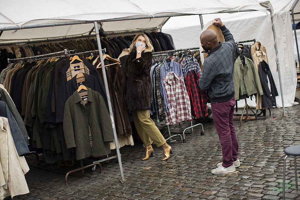 "A customer, wearing a face mask to fight against the spread of the coronavirus, tries on a coat at Marolles flea market in Brussels, Tuesday, Oct. 13, 2020. Authorities in Belgium, one of the European countries hit hardest by the coronavirus, are warning that the number of cases is rising at a ""quite alarming"" rate and that 10.000 people could be catching the virus each day by the end of the week. (AP Photo/Francisco Seco)"