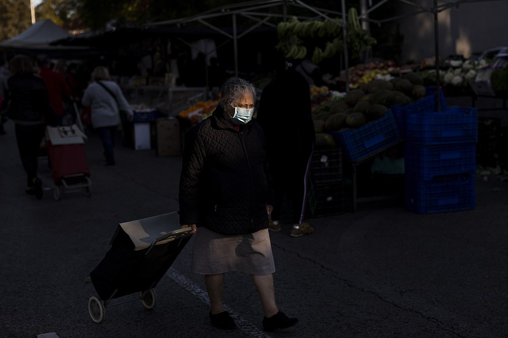 An elderly woman wearing a face mask to prevent the spread of coronavirus walks along street stalls at a fruit market in Madrid, Spain, Tuesday, Oct. 13, 2020. (AP Photo/Bernat Armangue)