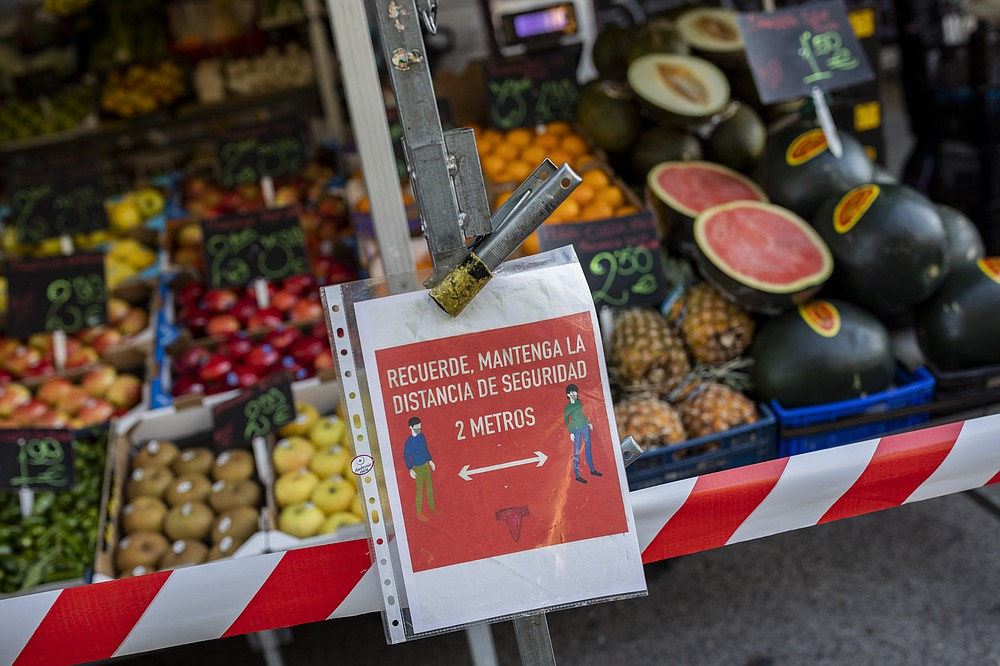 "A sign of social distancing guidelines hangs on a street stall in a market in Madrid, Spain, Tuesday, Oct. 13, 2020. The sign reads in Spanish ""Remember, keep a safe distance 2 meters"". (AP Photo/Bernat Armangue)"