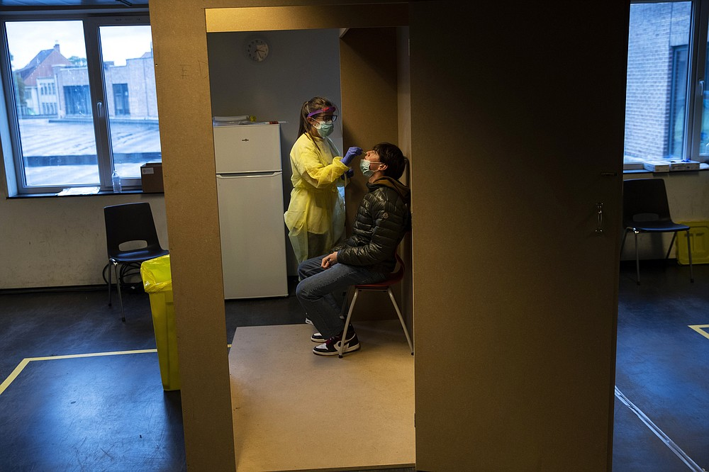 "A medical worker, wearing full protective gear, takes a nose swab from a patient to be tested for COVID-19 in a Red Cross test centre in Brussels, Tuesday, Oct. 13, 2020. Authorities in Belgium, one of the European countries hit hardest by the coronavirus, are warning that the number of cases is rising at a ""quite alarming"" rate and that 10.000 people could be catching the virus each day by the end of the week. (AP Photo/Francisco Seco)"