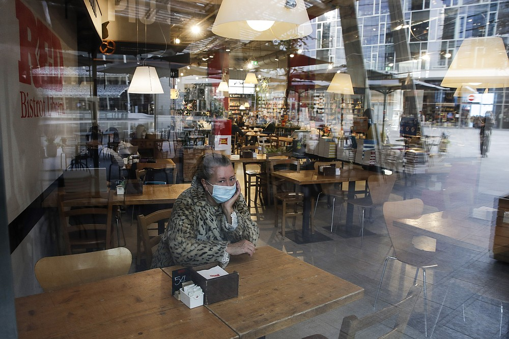 A woman sits in a cafe in Milan, Italy, Tuesday, Oct. 13, 2020. Italian Premiere Giuseppe Conte ordered strict new anti-COVID measures early Tuesday, including limits on private gatherings and a ban on casual pickup sports. Bars and restaurants must close at midnight, and drinks can only be consumed at tables -- not standing at the bar or outside -- after 9 p.m. (AP Photo/Luca Bruno)