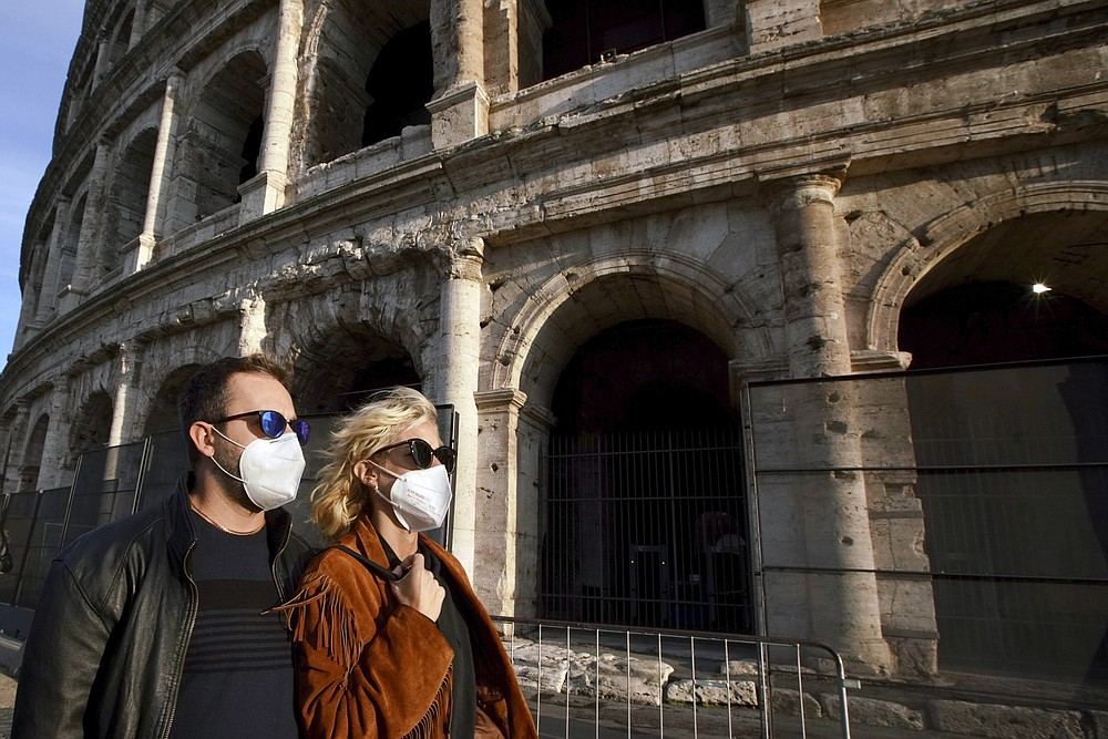 "People wearing masks walk past the ancient Colosseum in Rome, Tuesday, Oct. 13, 2020. Italian Premier Giuseppe Conte says the aim of Italy's new anti-virus restrictions limiting nightlife and socializing is to head off another generalized lockdown. Conte defended the measures as both ""adequate and proportional"" to the current need. He spoke Tuesday as the health ministry reported another 5,901 people tested positive over the past day and 41 people died, bringing Italy's official COVID-19 death toll to 36,246, the second highest in Europe after Britain. (AP Photo/Andrew Medichini)"