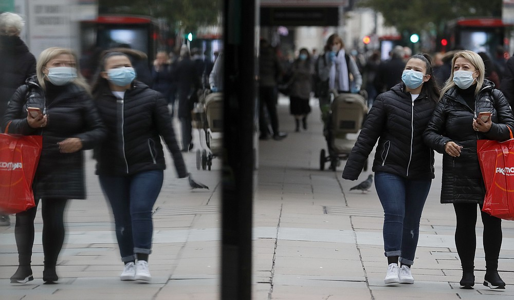 Shoppers walk along Oxford Street in London, Tuesday, Oct. 13, 2020. Unemployment across the U.K. rose sharply in August which is a clear indication that the jobless rate is set to spike higher when a government salary-support scheme ends this month and new restrictions are imposed on local areas to suppress a resurgence of the coronavirus. (AP Photo/Frank Augstein)