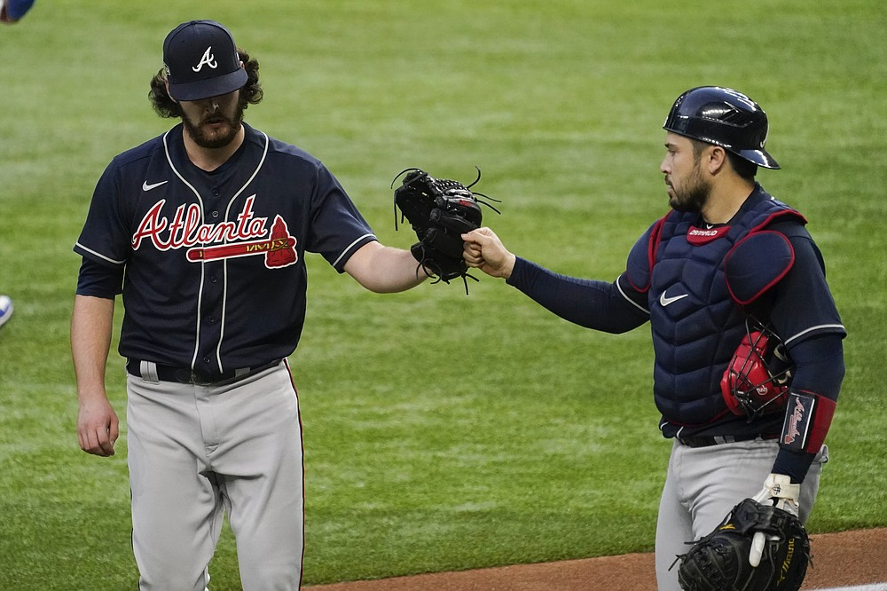 Atlanta Braves starting pitcher Ian Anderson and catcher Travis d'Arnaud celebrate the end of the fourth inning in Game 2 of a baseball National League Championship Series against the Los Angeles Dodgers Tuesday, Oct. 13, 2020, in Arlington, Texas. (AP Photo/Tony Gutierrez)