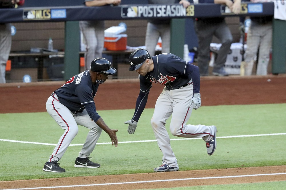 Atlanta Braves first baseman Freddie Freeman celebrates his two-run home run with third base coach Ron Washington against the Los Angeles Dodgers during the fourth inning in Game 2 Tuesday, Oct. 13, 2020, in the best-of-seven National League Championship Series at Globe Life Field in Arlington, Texas. (Curtis Compton/Atlanta Journal-Constitution via AP)