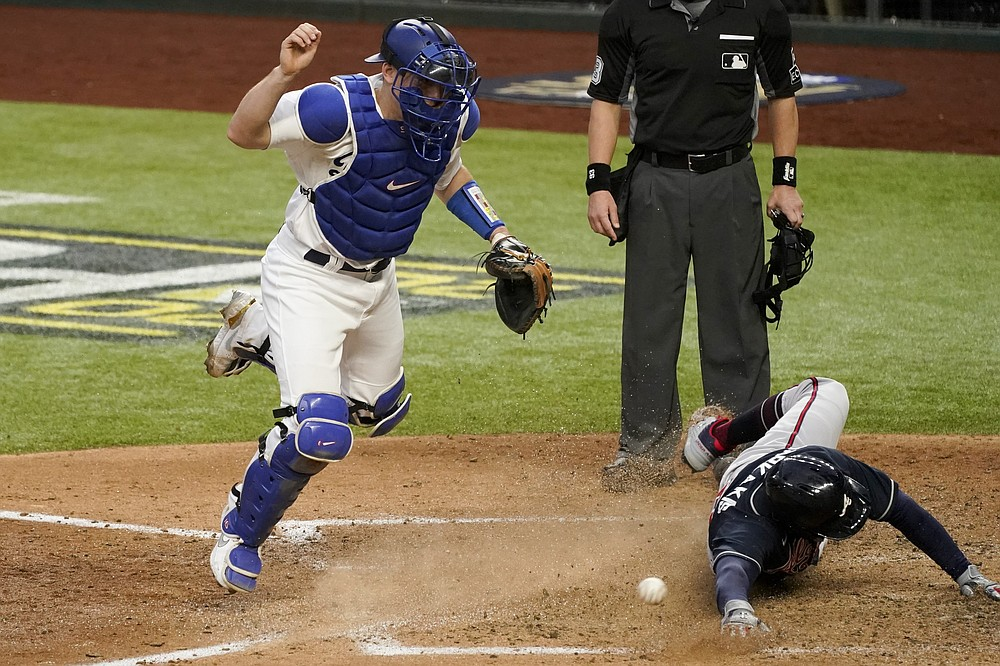 Atlanta Braves' Nick Markakis scores past Los Angeles Dodgers catcher Will Smith on a double by Cristian Pache during the fifth inning in Game 2 of a baseball National League Championship Series Tuesday, Oct. 13, 2020, in Arlington, Texas. (AP Photo/Tony Gutierrez)