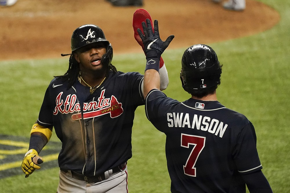 Atlanta Braves' Ronald Acuna Jr. celebrates after scoring on a walk by Travis d'Arnaud during the fifth inning in Game 2 of a baseball National League Championship Series against the Los Angeles Dodgers Tuesday, Oct. 13, 2020, in Arlington, Texas. (AP Photo/Tony Gutierrez)