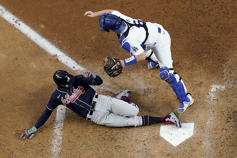 Atlanta Braves' Nick Markakis scores past Los Angeles Dodgers catcher Will Smith on a double by Cristian Pache during the fifth inning in Game 2 of a baseball National League Championship Series Tuesday, Oct. 13, 2020, in Arlington, Texas.(AP Photo/David J. Phillip)