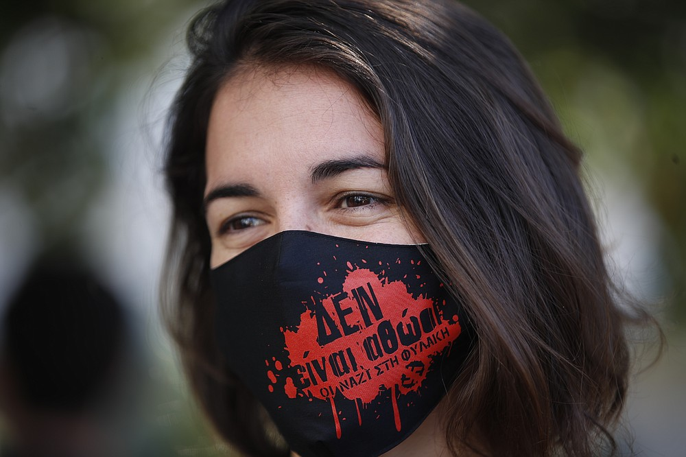 An anti-fascist protester, waring a mask to help prevent the spread of the coronavirus, gathers outside the court in Athens where the the sentencing announcement of the Golden Dawn trial, was schedule to be held, Wednesday, Oct. 14, 2020. The lengthy sentencing procedure is the final chapter in a more than five-year politically charged trial that encompassed four cases and involved 68 defendants, more than 200 witnesses and over 60 lawyers. The mask reads in Greek: 'Theyare not innocent, Nazis to prison'.(AP Photo/Thanassis Stavrakis)