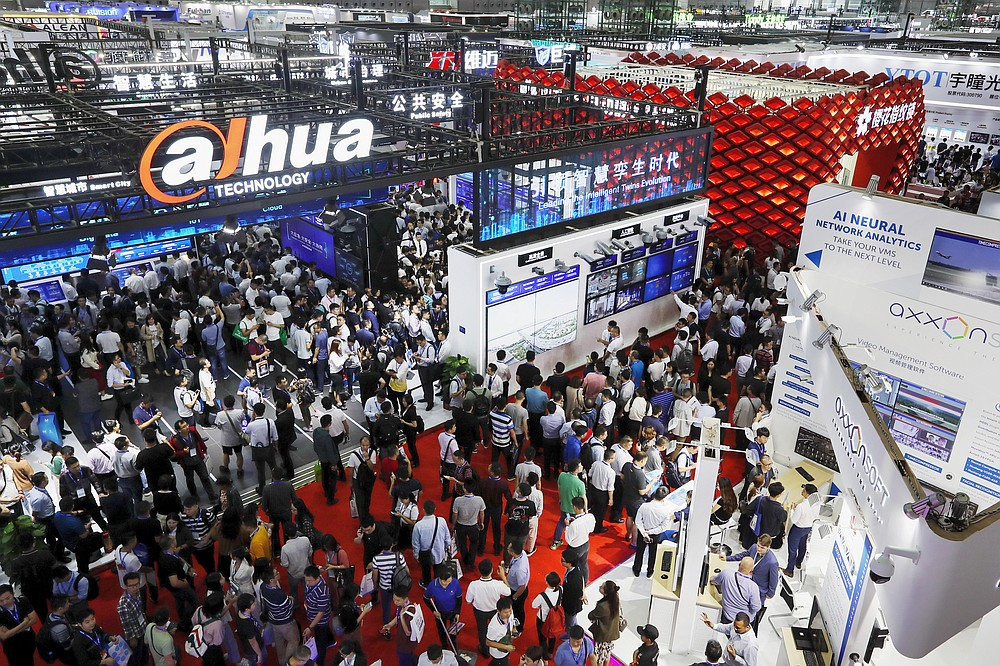 FILE - In this Oct. 29, 2019, file photo, visitors tour exhibitor booths showcasing their security systems at the China Public Security Expo in Shenzhen, China's Guangdong province. President Xi Jinping on Wednesday, Oct. 14, 2020, promised new steps to promote development of China's biggest tech center, Shenzhen, amid a feud with Washington that has disrupted access to U.S. technology and is fueling ambitions to create Chinese suppliers. (AP Photo/Andy Wong, File)