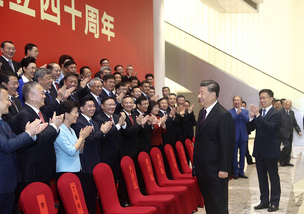 In this photo released by China's Xinhua News Agency, Chinese President Xi Jinping reacts as attendees applaud during an event to commemorate the 40th anniversary of the establishment of the Shenzhen Special Economic Zone in Shenzhen in southern China's Guangdong Province, Wednesday, Oct. 14, 2020. President Xi Jinping promised Wednesday new steps to back development of China's biggest tech center, Shenzhen, amid a feud with Washington that has disrupted access to U.S. technology and is fueling ambitions to create Chinese providers. (Ju Peng/Xinhua via AP)