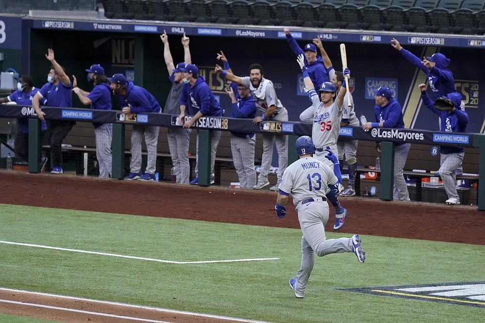 Los Angeles Dodgers' Max Muncy (13) celebrates his grand slam home run during the first inning in Game 3 of a baseball National League Championship Series against the Atlanta Braves Wednesday, Oct. 14, 2020, in Arlington, Texas. (AP Photo/Tony Gutierrez)