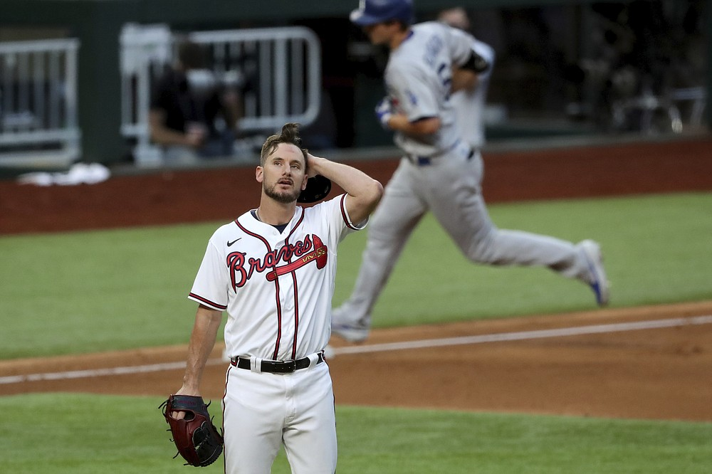 Atlanta Braves relief pitcher Grant Dayton, center, reacts after giving up a solo home run to Los Angeles Dodgers shortstop Corey Seager during the third inning in Game 3 of a baseball National League Championship Series Wednesday, Oct. 14, 2020, in Arlington, Texas.  (Curtis Compton/Atlanta Journal-Constitution via AP)